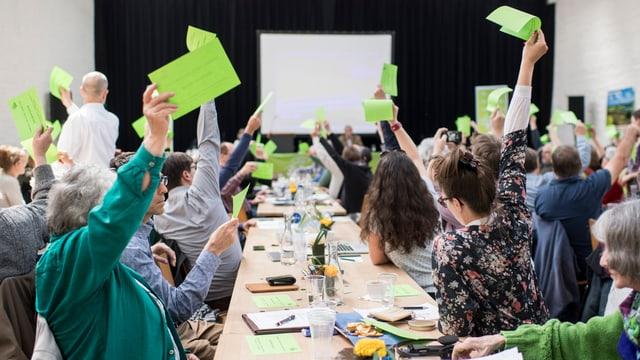 Personen halten grüne Stimmzettel in die Höhe.