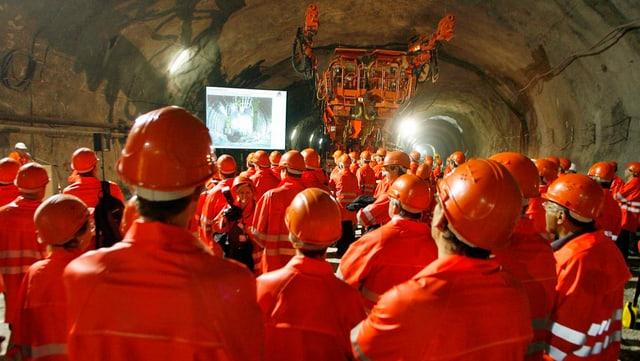 Eine Gruppe Menschen in organgen Gewändern und Helmen im Stollen der Neat-Baustelle.