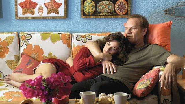 Ein Mann und eine Frau kuscheln zusammen auf einem bunten Sofa.