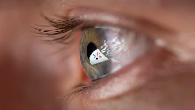 Zwei Pokerkarten-Asse spiegeln sich in einem Auge.