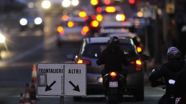 An der Grenze. Autos und Motos stehen Schlange. Auf einem Schild steht frontalieri und altri. Es ist abends.