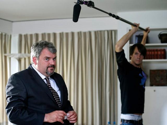 Müller steht in einem Wohnzimmer, im Hintergrund der Tontechniker mit einem Stabmikrofon.