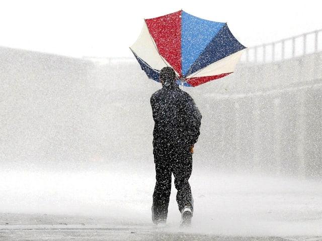 Eine Person steht im Regen. Der Regenschirm wird vom Wind verblasen.