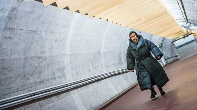 Ein Mann in dickem Mantel schreitet durch einen Tunnel.