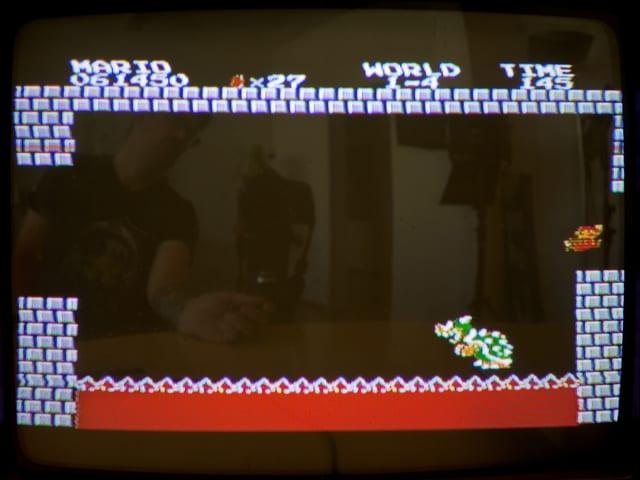 Mario zieht ihm den Boden unter den Füssen weg. Der Dino fällt in die Lava.