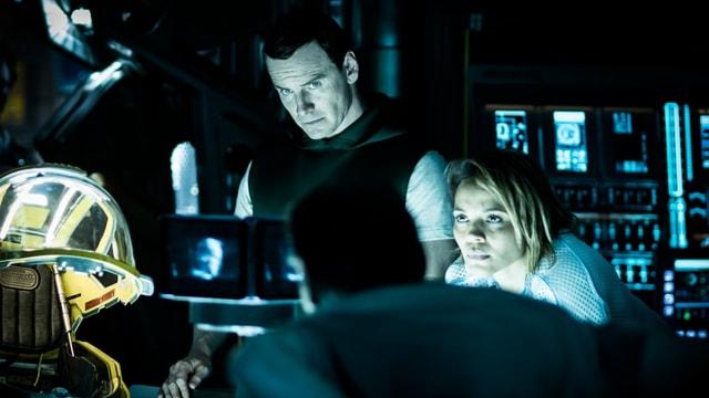 Ein menschenähnlicher Roboter und eine Frau im Raumschiff-Cockpit.