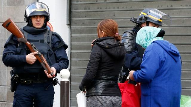 Zivilisten werden von Polizisten angehalten und kontrolliert.