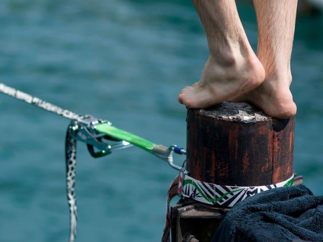Zwei Füsse auf einem Pfosten, ein gespanntes Seil über Wasser