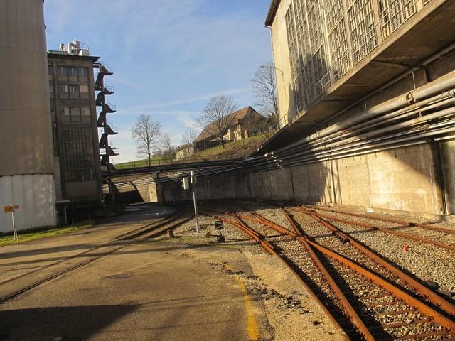 Blick über alte Bahngeleise zu einigen baufälligen Fabrikgebäuden.