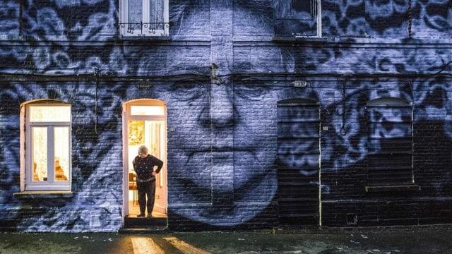 Ein Porträt einer Frau klebt an einer Fassade. Die Frau selbst steht in der Tür.