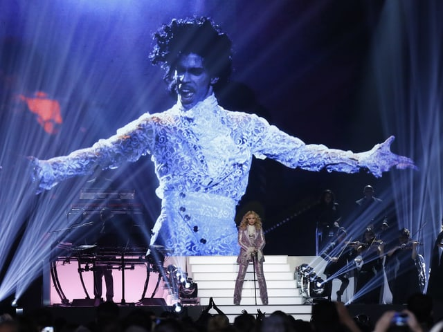 Madonna auf der Bühne vor einer grossen Projektion von Prince