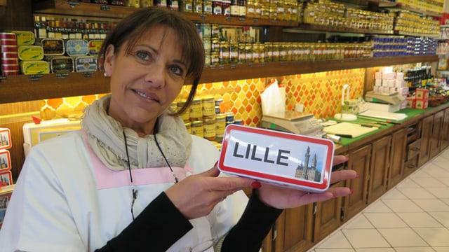 Coralie hät ein Souvenir mit der Aufschrift Lille hoch.