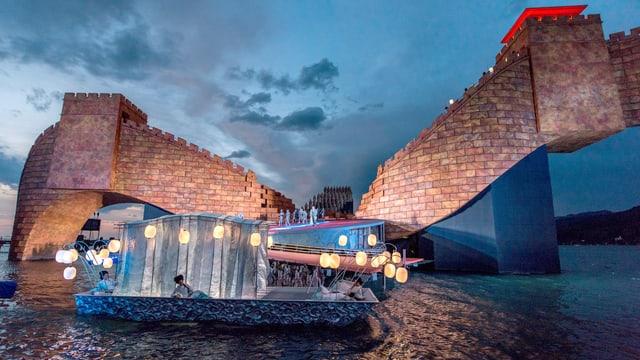 Eine Opernbühne auf dem Wasser, im Hintergrund eine beleuchtete Mauer.