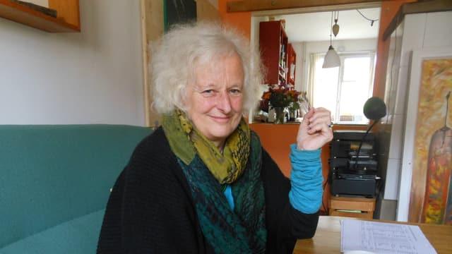Schlummermutter Syliva Frey Werlen sitzt auf einer grünen Couch in ihrem Wohnzimmer.