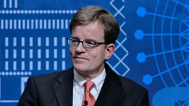 Porträt eines Mannes in Anzug und Brille, er blickt rechts von sich und lächelt halbwegs.