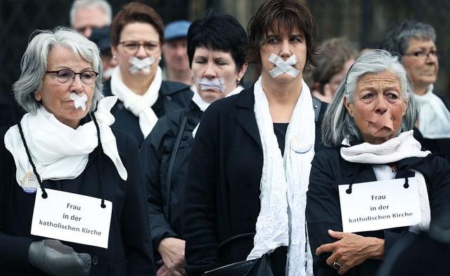 Frauen protestieren: ihre Münder sind mit Klebeband zugeklebt.