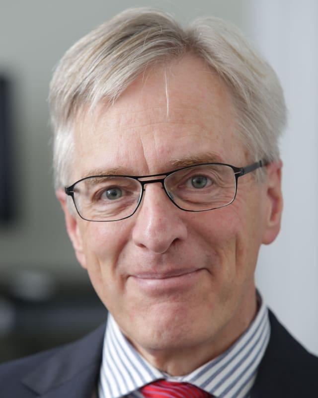 Professor Ulrich Schnyder, Direktor der Klinik, mit weissen, kurzen Haaren, schwarzer Brille mit dünnem Rand und einem Lächeln.