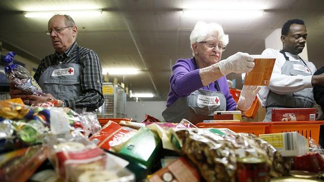 Zwei Männer und eine Frau sortieren Lebensmittel.