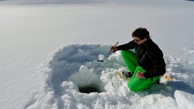 Ein Eisfischer kniet im Schnee und hält eine kurze Angelrute in den Händen.