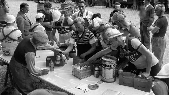 Fahrer der Tour de Suisse 1938 holen sich an einem Verpflegungsstand neue Ovomaltine-Bidons, Ovomaltine-Riegel und Traubenzucker.