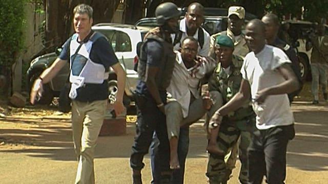 Sicherheitskräfte tragen eine verletzte Geisel weg.
