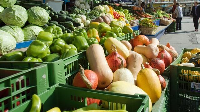 Grüne Kisten gefüllt mit Gemüse stehen auf einem Markt.