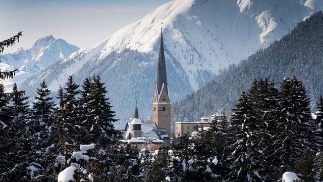 Eine Kirch in Davos mit vor verschneiter Bergkulisse.