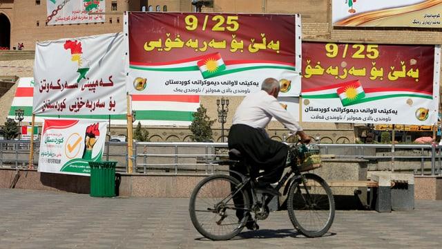 Velofahrer vor Plakaten