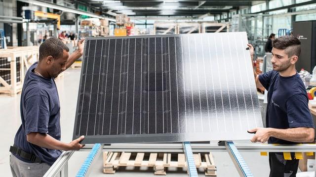 Arbeiter bei Meyer Burger halten ein Solarmodul in den Händen (in der Fabrikationshalle)
