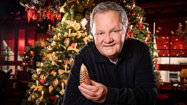 Der Moderator steht vor einem reich geschmückten Weihnachtsbaum und hält einen goldenen Tannzapfen in der Hand.