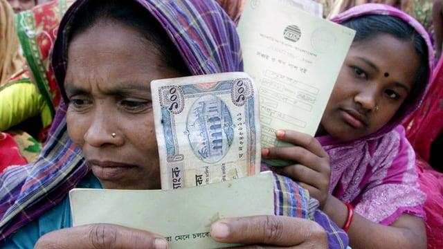 Frauen mit Geld und Vertrag in der Hand.