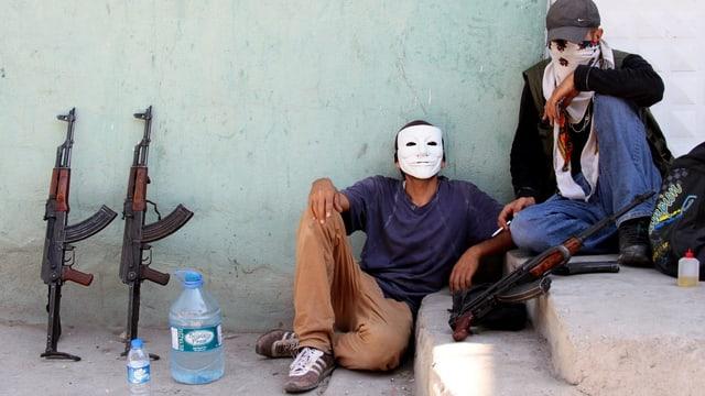 Zwei Männer mit Masken auf einer Treppe, links daneben zwei Gewehre.