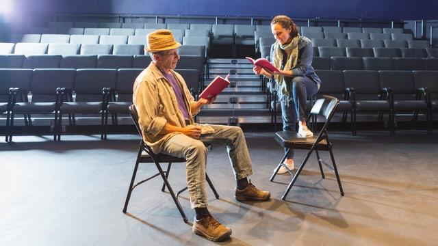 Ein Mann und eine Frau sitzen im leeren Theatersaal und halten ein Heft ind en Händen.