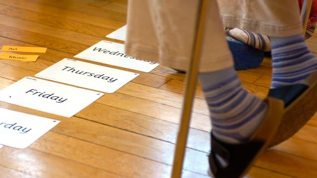 Wochentage auf Englisch liegen am Boden vor den Schülern