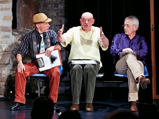 Daniel Buser, Roland Sutter und Walo Niedermann sitzen auf einem Bänkli.