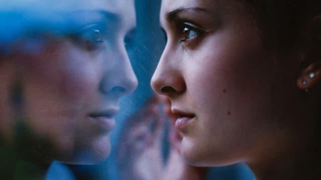 Eine Frau blickt in eine Scheibe.