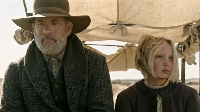 Tom Hanks und Helena Zengel, frontal fotografiert in einer Kutsche.