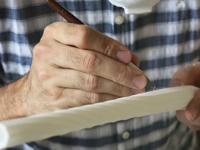 Ein Mann schneidet an einem Instrument herum.