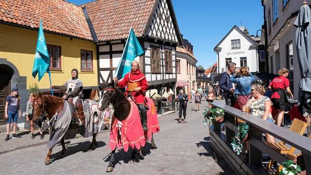 Zwei Ritter auf Pferden mit Flaggen in einem Touristendorf in Schweden.