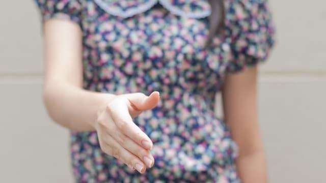 Mädchen, das die Hand reicht.