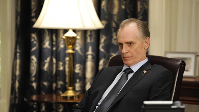Ein Mann mit grauem Haar sitzt in Anzug und Kravatte in einem Bürosessel.