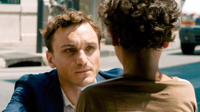 Georg (Franz Rogowski) blickt tief in die Augen eines Kinds.