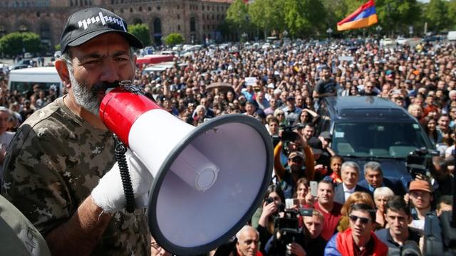 Nikol Paschinjan mit Megaphon vor einer Menschenmenge.