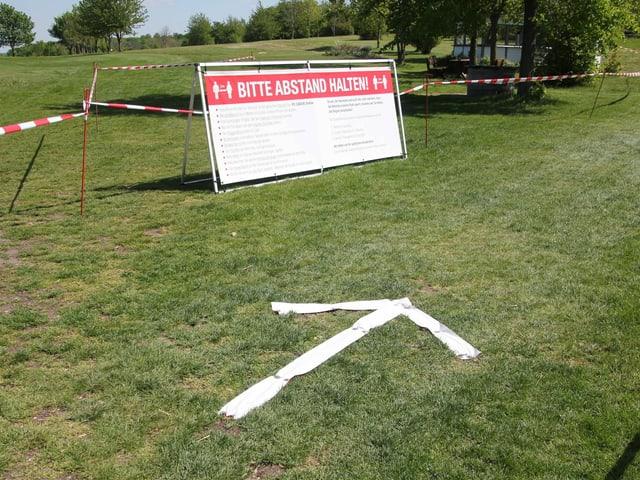 Ein Schild, auf dem gebeten wird, Abstand zu halten.