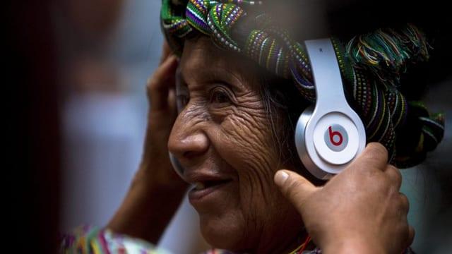 Eine Indigene mit Kopfhörern.