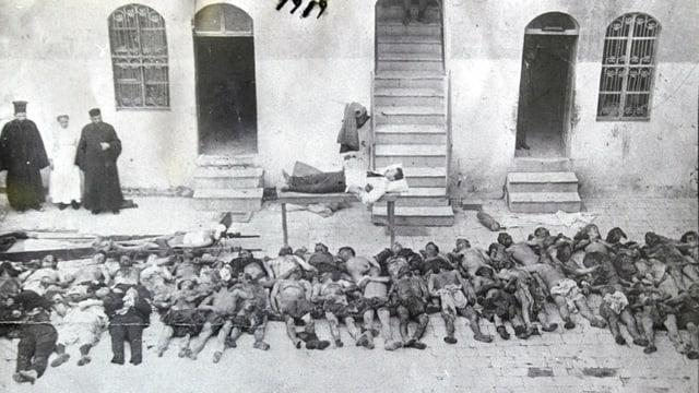 Ein Türke macht auf einer Pritsche einen Mittagsschlaf. Unter ihm tote Armenier.
