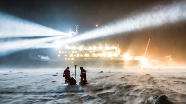 Zwei Meereisphysiker arbeiten auch bei Wind und Schneedrift. Es ist Nacht.