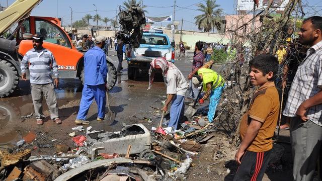 In Diwaniya räumen die Anwohner die Trümmer weg, nachdem in den Morgenstunden eine Autobombe detoniert war.