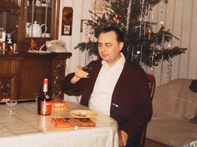Ein Mann sitzt am Tisch mit einem Glas Likör, im Hintergrund ein geschmückter Weihnachtsbaum.