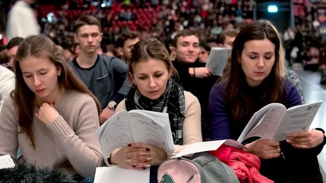 Drei junge Frauen sitzen in einem grossen Raum mit anderen, sie halten Papiere in der Hand.